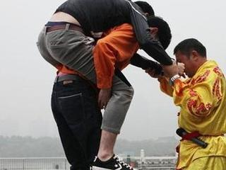 China's Zhang is walking by wearing iron shoes of 123kg & carrying 2 persons in Xi'an