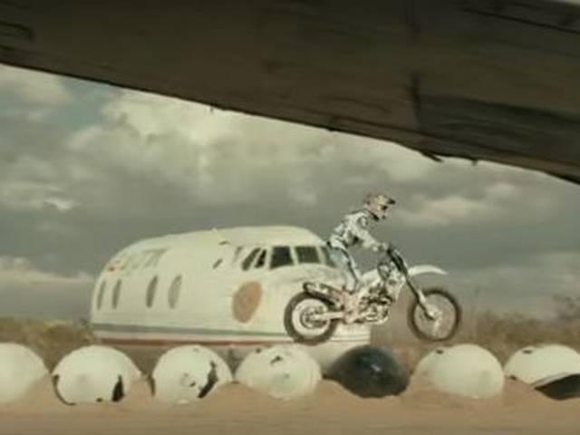 man performs stunt bike riding bike on plane