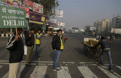 A member of civil defense holds roses and others hold placards at a traffic intersection to raise awareness about the fifteen days experiment to reduce the number of cars in its efforts to fight pollution in New Delhi, India, Friday, Jan. 1, 2016. New Delhi is testing a formula where private cars will be allowed on the roads only on alternate days from Jan. 1-15, depending on whether their license plates end in an even or an odd number. (AP Photo/Altaf Qadri)