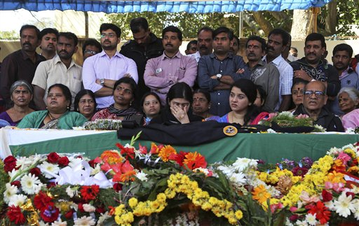 Wife Radhika, center, gestures as she sits next to the coffin of her husband and India's National Security Guard commando, Niranjan Kumar, who was among those killed in the attack on the Pathankot air force base after the body was brought to Bangalore, India, Monday, Jan. 4, 2016. At least two gunmen were holed up in a two-story building on the Indian air force base near the Pakistan border and exchanging gunfire with troops Monday, more than two days after they and several others attacked the heavily fortified compound, officials said. (AP Photo/Aijaz Rahi)
