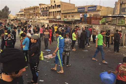 People gather at the scene of deadly bombing attacks in Sadr City, Baghdad, Iraq, Sunday, Feb. 28, 2016. Militants attacked Mredi outdoor market on Sunday in eastern Baghdad, killing at least 24 people and wounding dozens, officials said. Minutes later, a suicide bomber blew himself up amid the crowd that had gathered at the site of the first bombing, he added. (AP Photo/Ali Abdul Hassan)