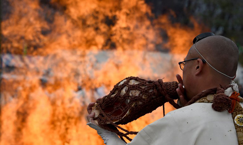 "Buddhist monks pray beside flaming wood before walking barefoot over the fire during the traditional ""hi-watari"""