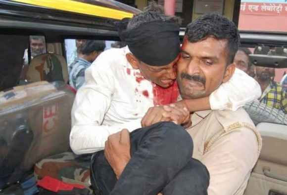 UP Police staff carries injured man for treatment