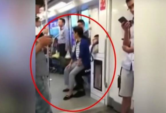 woman sit in man lap after he refuse to give seat in metro
