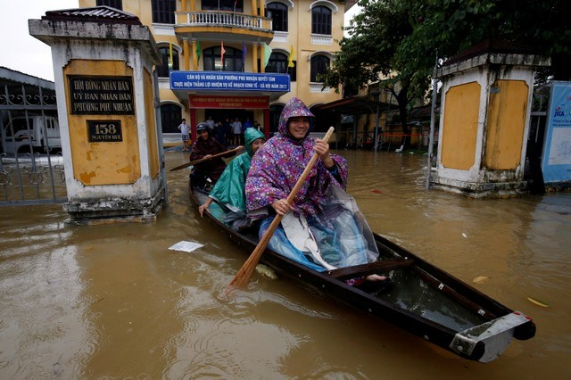 Officials sail a boat out of a submerged local government building after typhoon Damrey hits Vietnam in Hue city