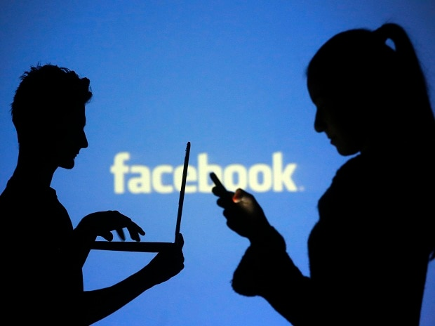 People pose with laptops in front of projection of Facebook logo in this picture illustration taken in Zenica